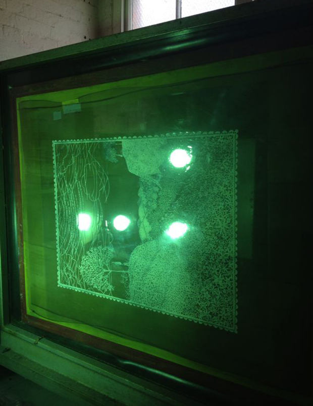 The photosensitive exposure unit: The spray painted paper cut oout is positioned on the silk screen which has been coated with a light sensitive photo emulsion. When the UV is exposed, the paper cut out will block out the coating. When Tom rinses the screen the emulsion will block out the screen where there were spaces in the paper cut out, meaning that ink will only pass through the silkscreen where the paper cut out allows it to.
