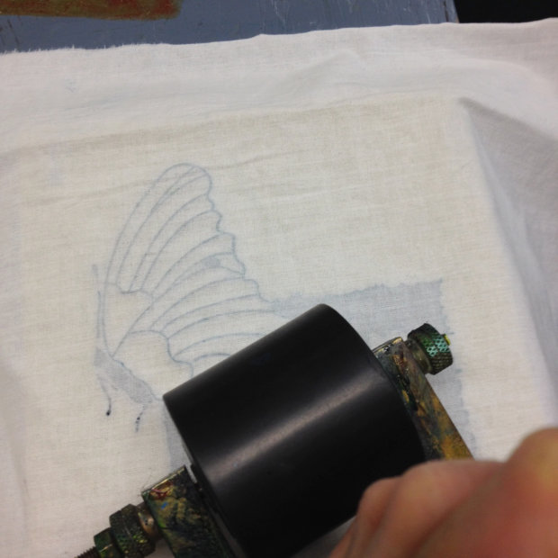 Applying pressure to the inked up block from the back of the fabric being printed on