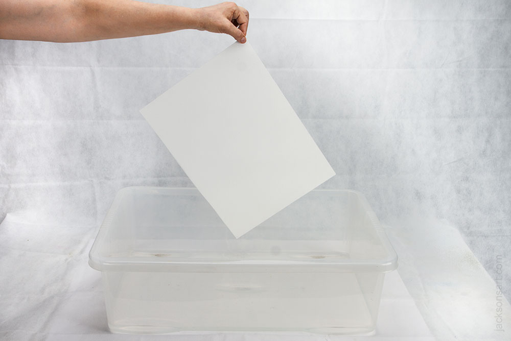 Remove the paper from the water by one corner and shake to see if it feels floppy like wet cloth. Then allow much of the water to drip away.