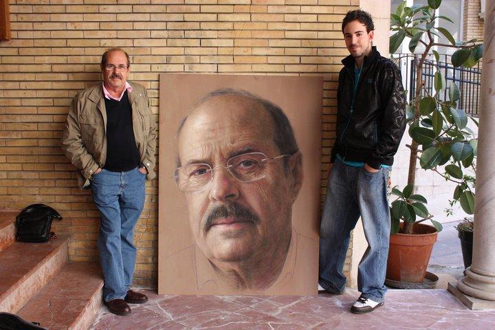 Professor D. Francisco Borras Cervera stands next to Ruben Belloso Adorno and his portrait at the Faculty of Fine Arts in Seville