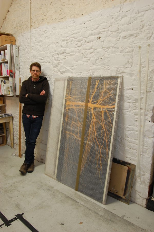 Andrew MacKenzie with one of the finished drawings in the studio