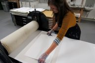 Jemma Gunning placing paper on to her inked up etching plate