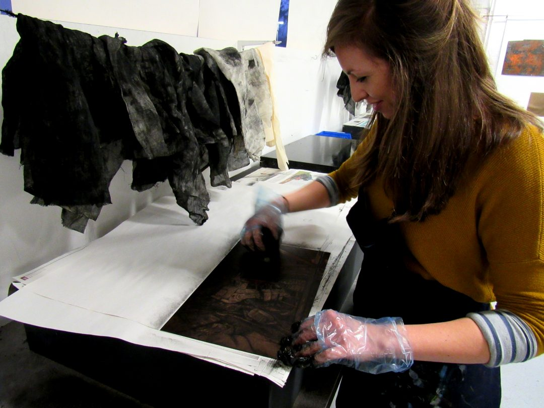Jemma Gunning wiping an etching plate - the ink that sits in the grooves of the etched lines remain and are printed while the rest is wiped away