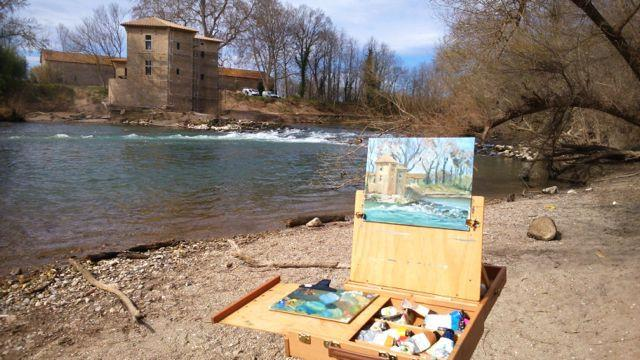 Plein air oil painting of a rustic building from across a river during Linda H Matthews painting holiday in France