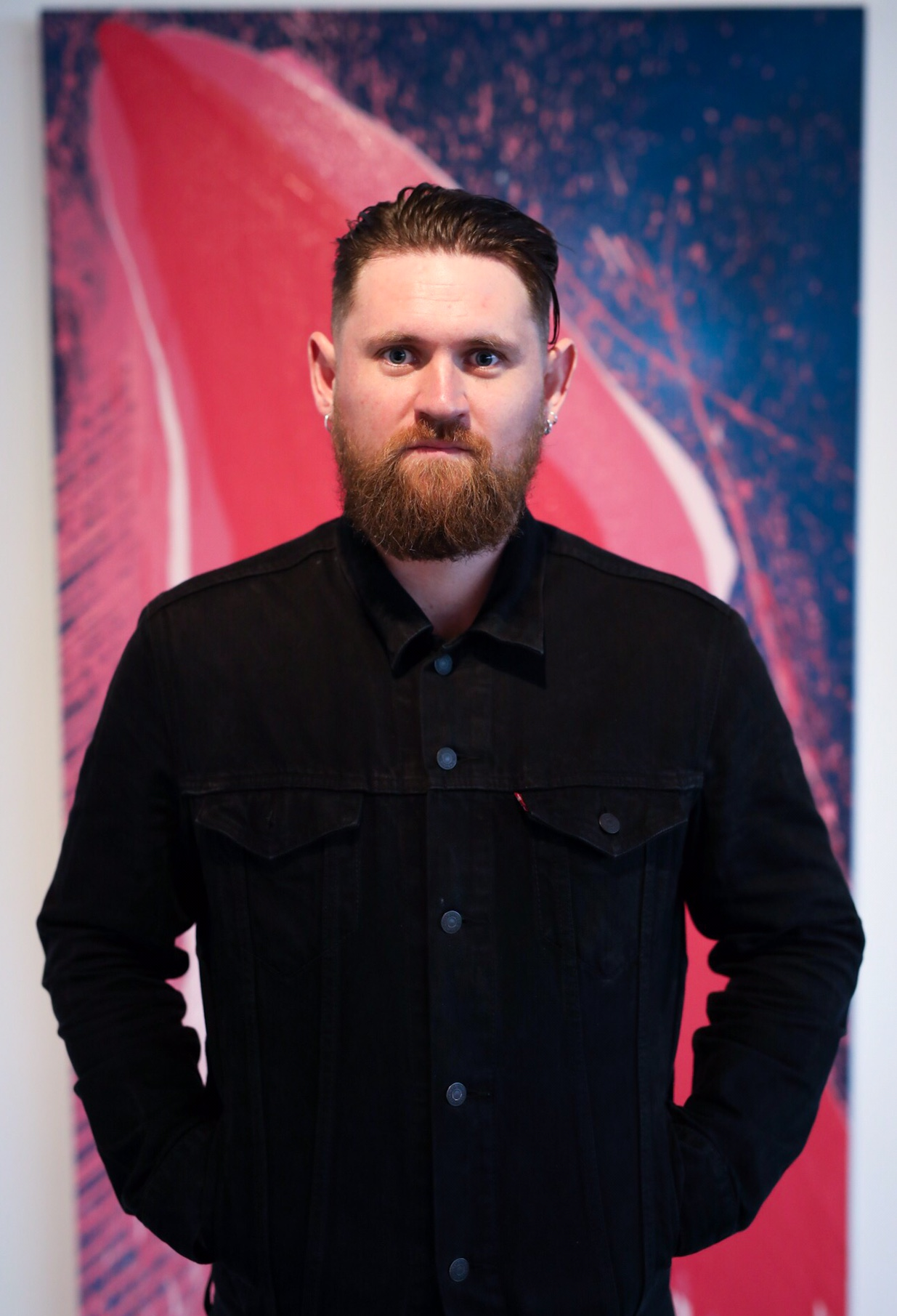 Eoin without hat in front of pink painting