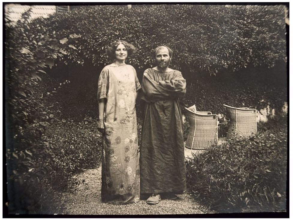 Emma Bacher. Gustav Klimt in his painter's coatand Emilie Flöge in a reform dress in the garden of the Villa Oleander, 1910Private collection, courtesy of Klimt Foundation, Vienna.