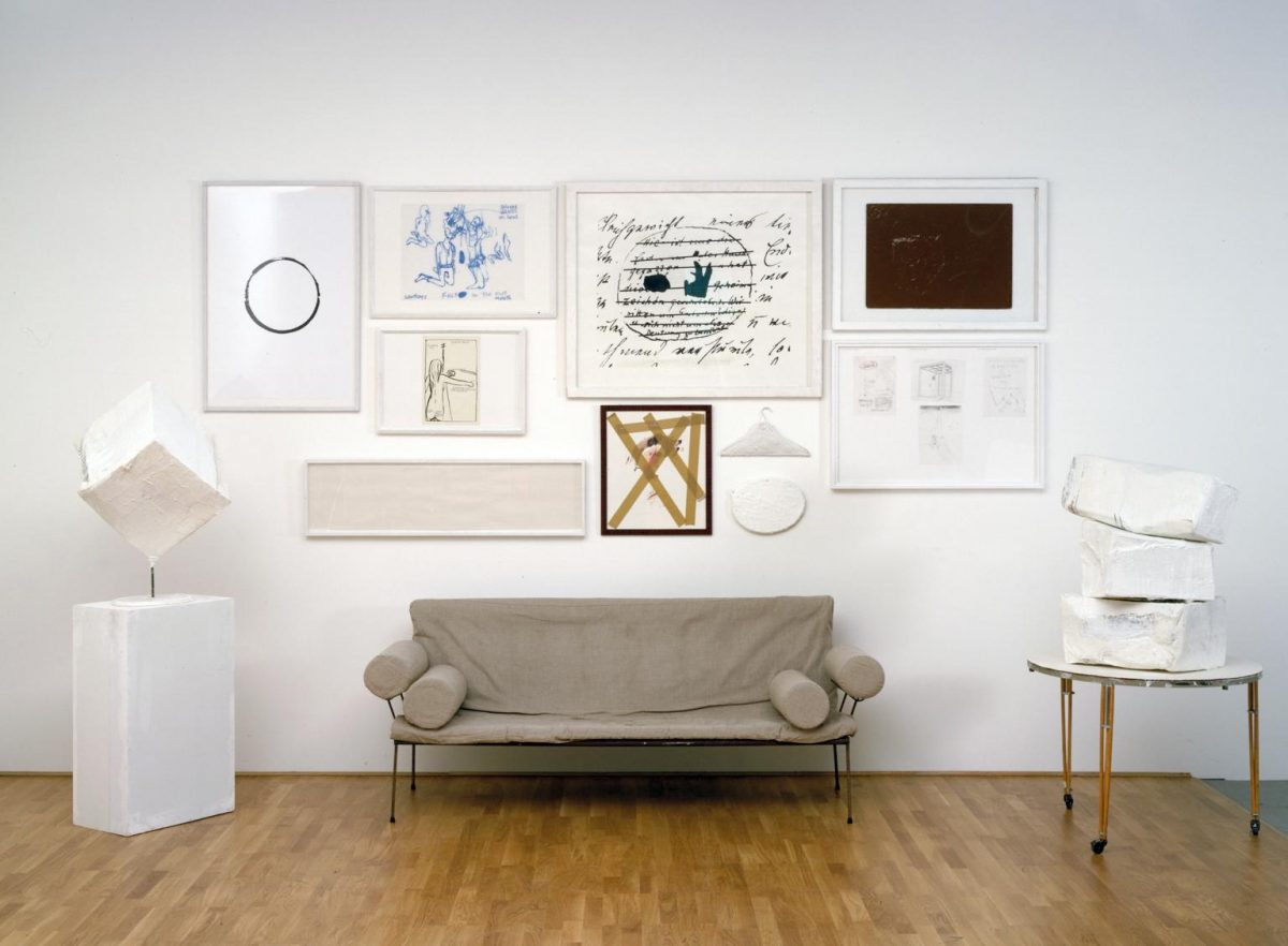 Franz West, Viennoiserie, 1998, Sofa, hardboard table, hardboard plinth, cardboard boxes, 2 wall pieces and 8 works on paper, overall dimensions approx: 294 cm x 524 cm x 128 cm