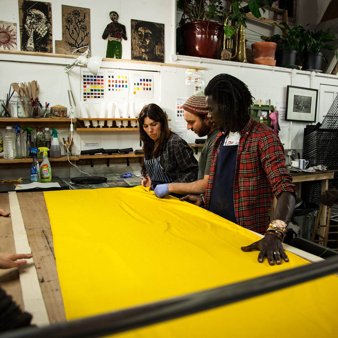 Printing a large format woodcut onto fabric at one of Cato Press' Community print nights